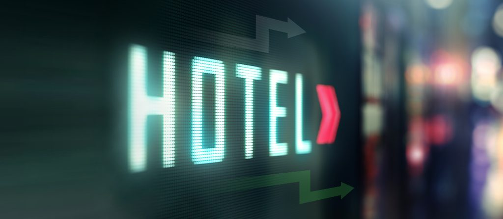 "A neon-lit sign reading ""hotel"""