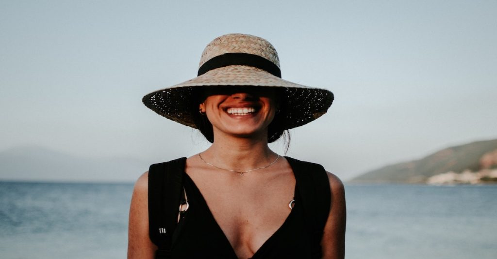 woman smiling wearing sun hat