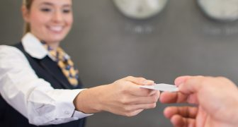 Staff handing hotel loyalty program card to guest