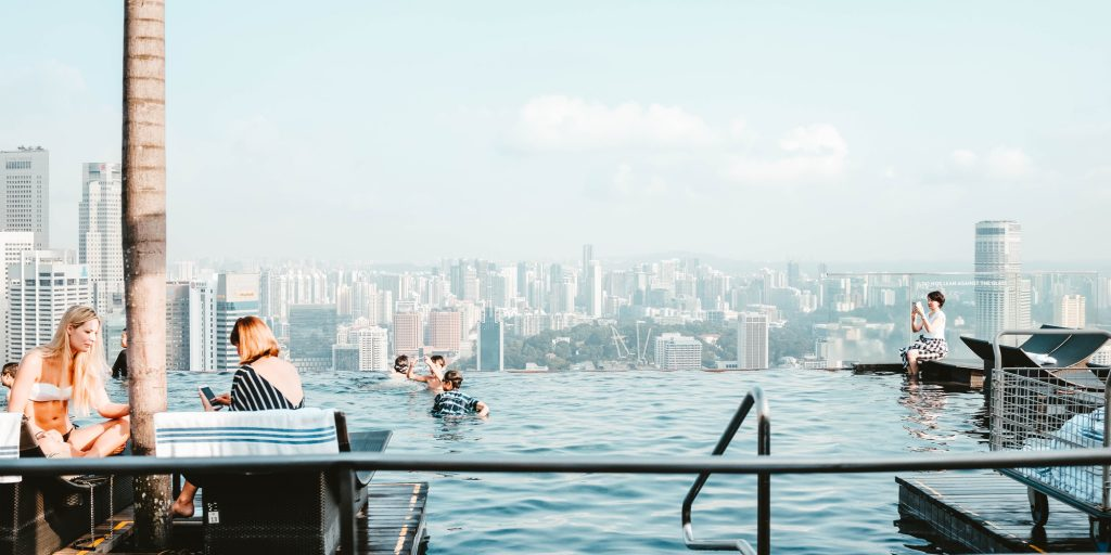 possible online advocates sat around infinity pool using smartphones