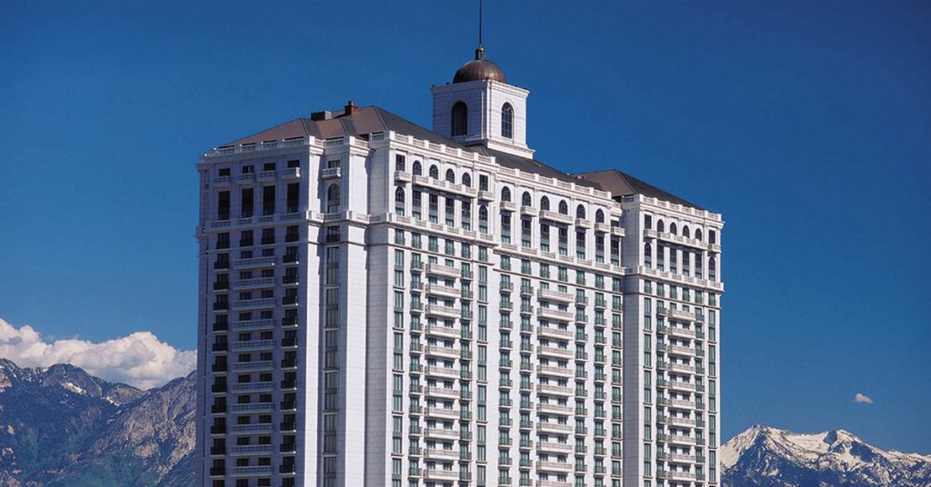 Large hotel on backdrop of blue sky and mountains, Grand America Hotels & Resorts - it is an upper midscale hotel