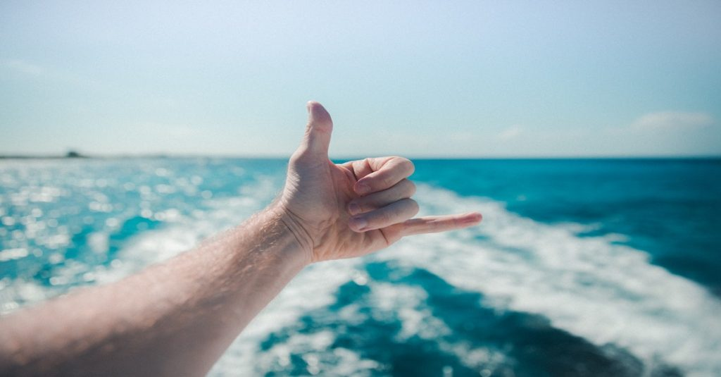 Man making hand gestures from a boat