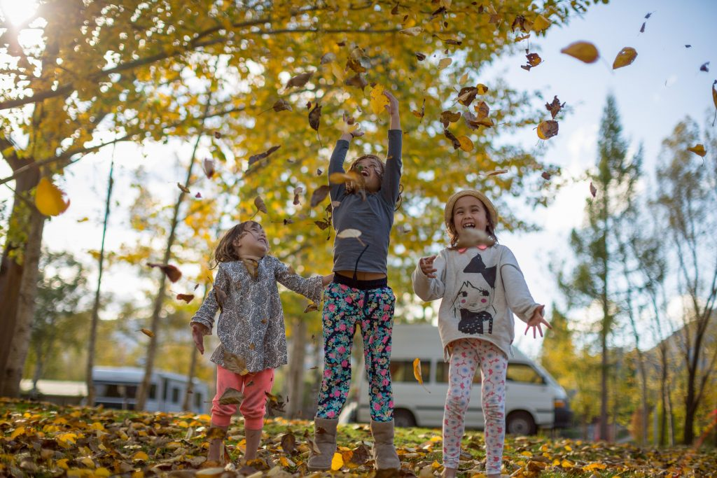Children playing with autumn leaves in a holiday park