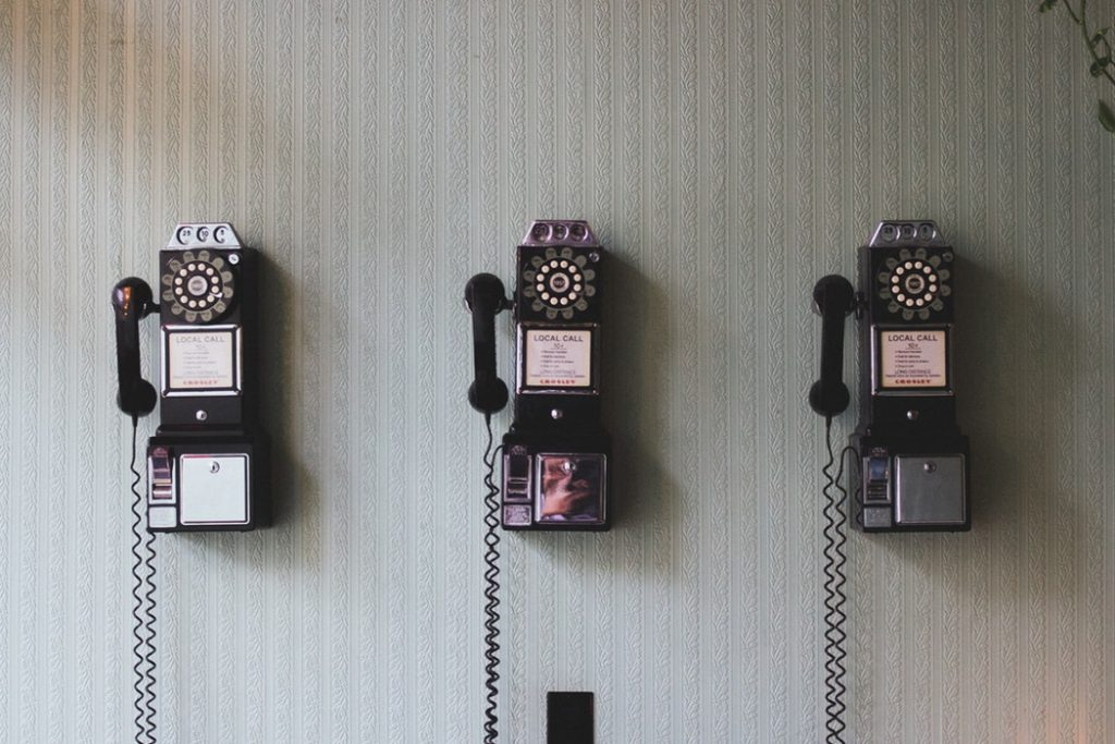 Three antique rotary phones hanging on the wall