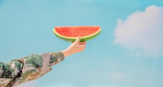 Woman holding slice of watermelon in summer