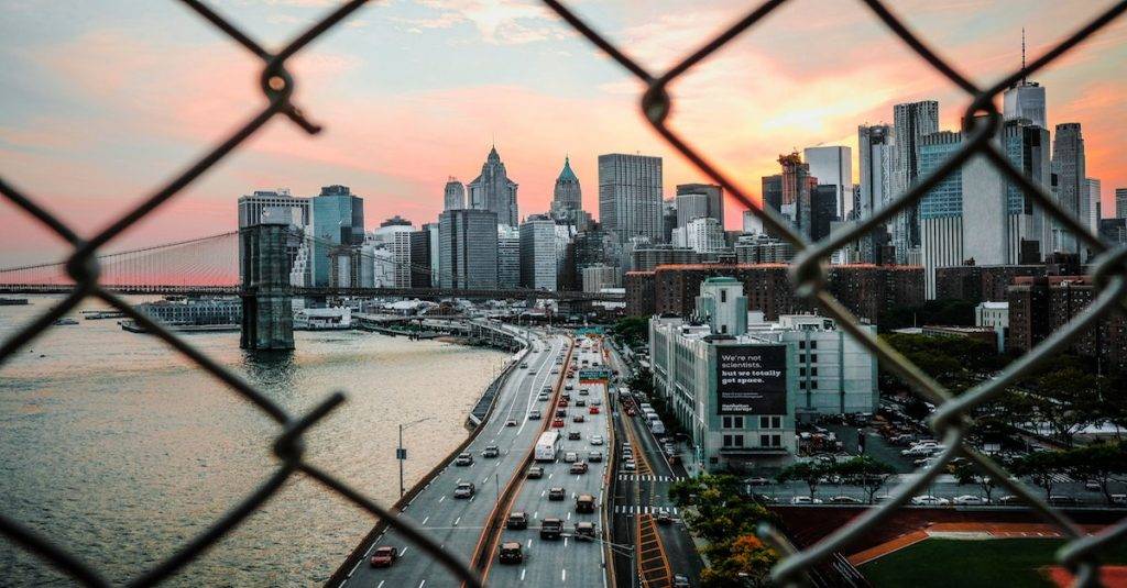 cityscape through barbed wire hole