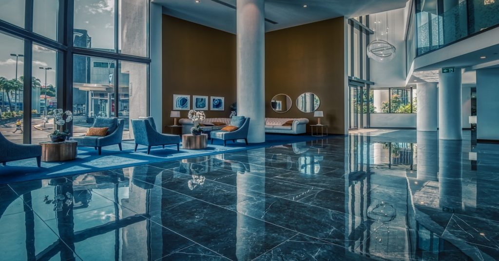 Vast modern hotel lobby with marble floor and large glass windows