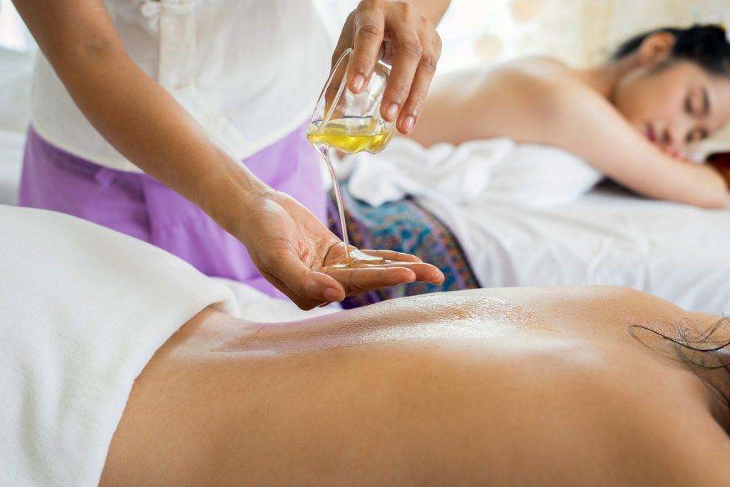 Two women receiving a relaxing massage with essential oils