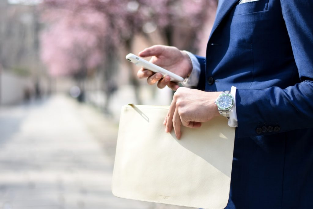 Man holding his wallet and staying connected using his phone in the other hand