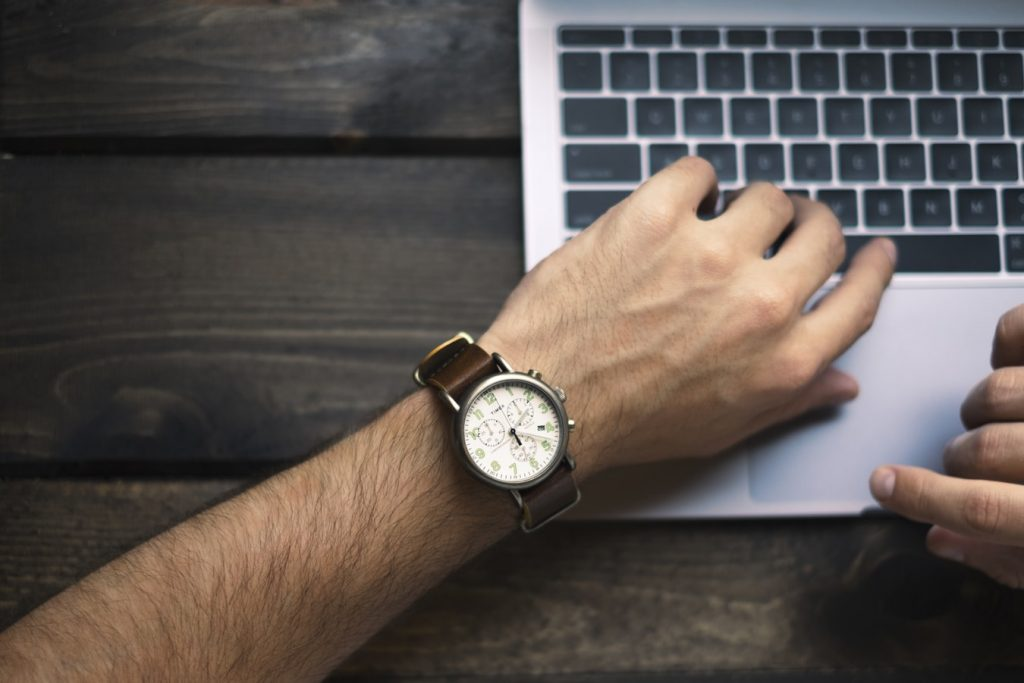 A man checks his watch whilst working, conscious of his review response time