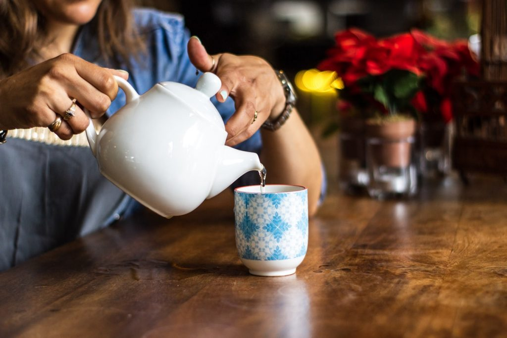 pouring water in to a decorated tea cup