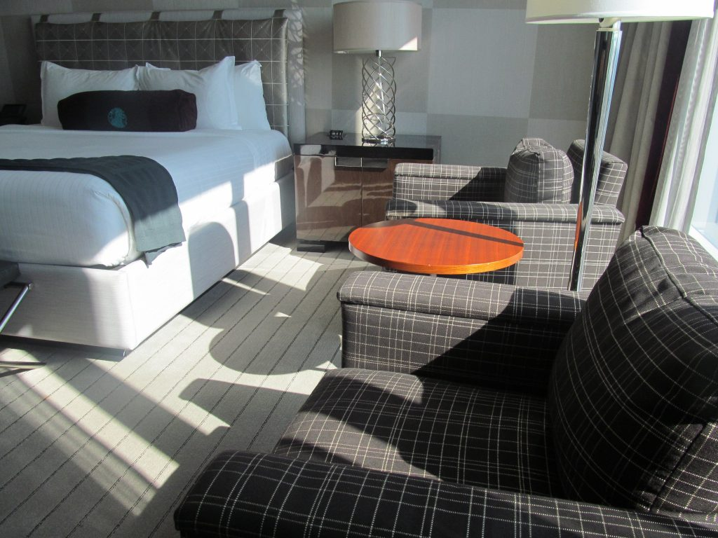 white and grey hotel room with the sunshine