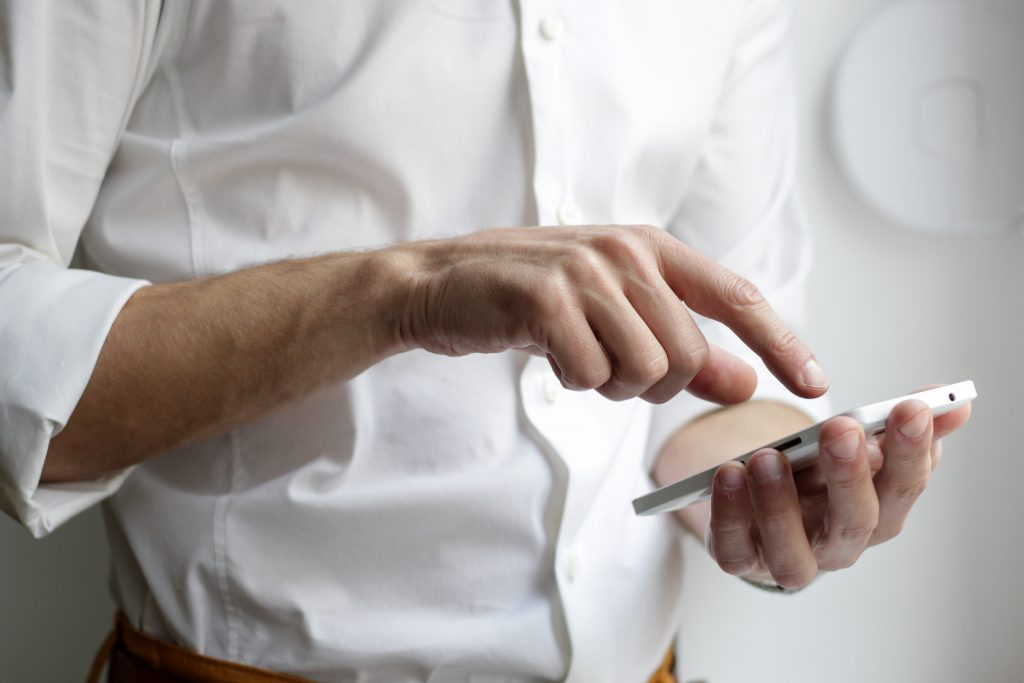 Businessman in shirt using his phone to check in to hotel