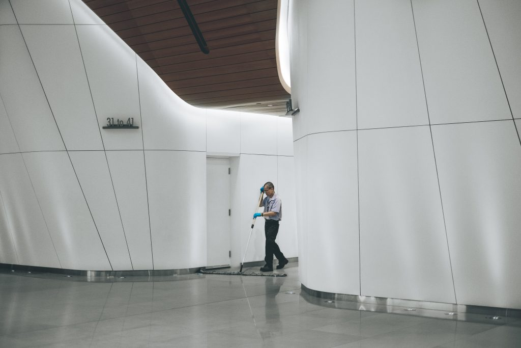 Man sweeping floor with gloves on