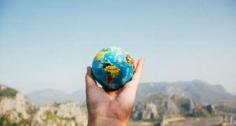 A person holding a globe looking for his next personalized guest experience